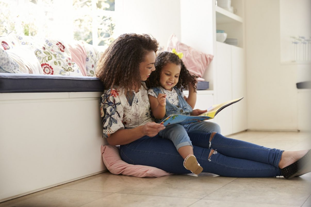 Image of a Mum reading a book with her child, both of whom are smiling